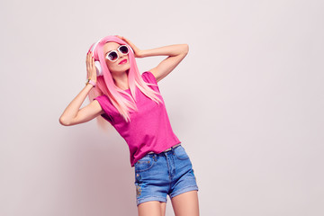 Wall Mural - Girl Listening Music in Headphones Having Fun. DJ vibrations. Young Model Woman with Kiss Face Expression, Pink Fashion Hairstyle in Stylish Trendy Summer Outfit.