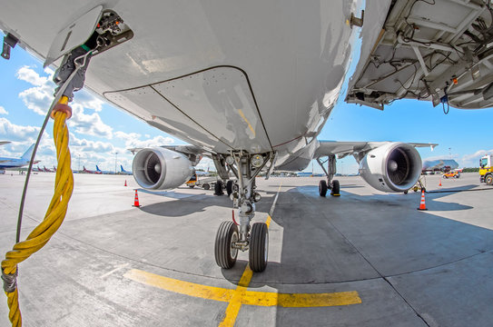 View of front chassis, wing and the big engine of the aircraft in the parking lot at the airport, ground-based power cable.
