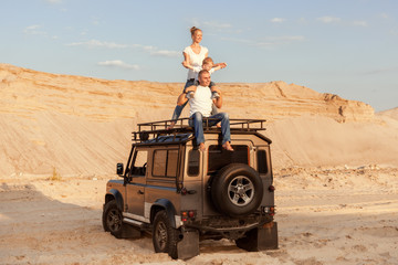 Young family with a child are sitting on the roof of a car in the desert.