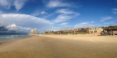 A panoramic view of a lonely romantic sand beach with a beautiful Mediterranean sea and high buildings on the horizon under the blue sky. The photo was shot in a public beach of Haifa, Israel.