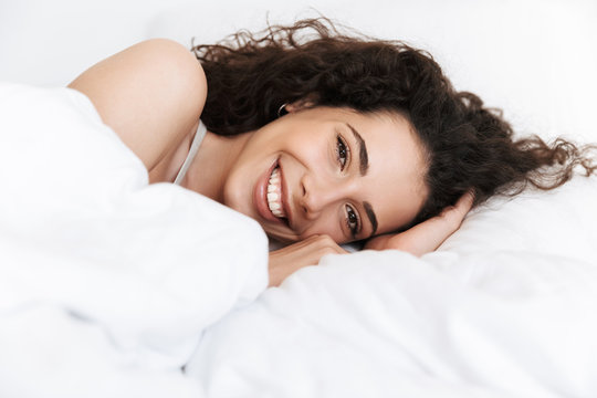 Portrait of gorgeous woman 20s with dark curly hair lying in bed on white linen, and smiling at camera