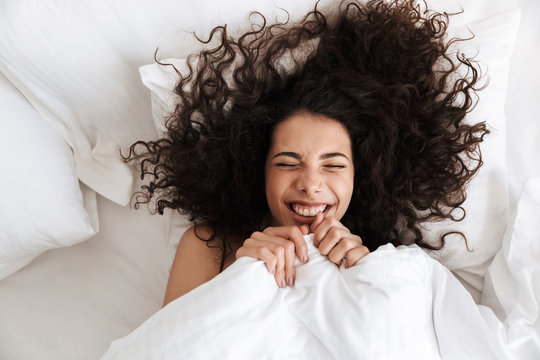 Portrait from above of cheerful woman 20s with dark curly hair screwing up her eyes, while lying in bed under white blanket with happy smile