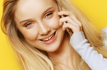 portrait of young, happy woman talking on phone looking at camera, over yellow background
