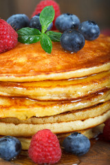 Stack of freshly baked american pancakes with maple syrup, blueberries and raspberries on top. Closeup image..