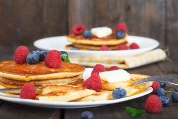 Sweet american breakfast. Buttermilk pancakes served hot with maple syrup and fresh berry fruit .