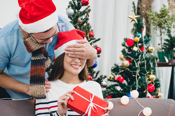 Asia lovers couple, boyfriend surprise girlfriendby giving Christmas present at sofa with xmas decoration tree at house party,Holiday festive celebrating season.