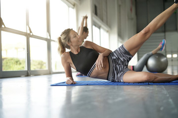 Beautiful blond woman at the gym doing pushups exercises
