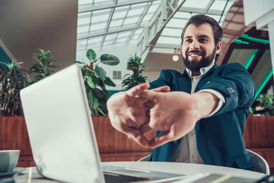Worker man exercising stretching arms in office.