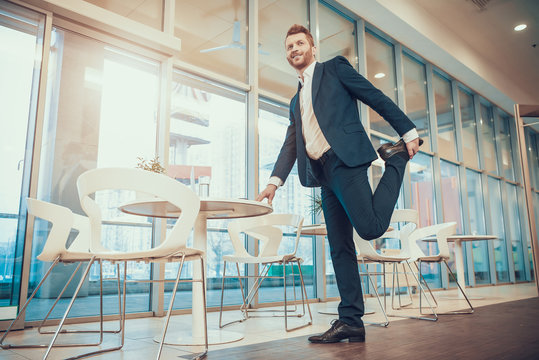 Worker stretching leg at table in office.