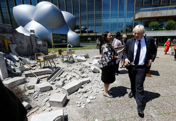 Britain's Foreign Secretary Johnson walks past a mockup of a bombed classroom in front of the Luminarium inflatable installation aside of the Human Rights Council at the United Nations in Geneva