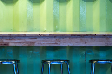 The empty wooden table with chairs  against green metal textures wall in the shop.