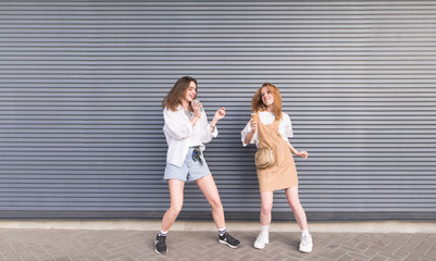 Photo Blinds Dance School Two young girlfriends in stylish clothes dance on a gray background. Portrait of two cheerful girls on the background wall.