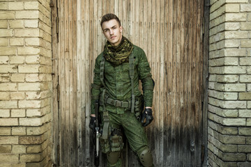 Young male military soldier with a rifle posing against wooden background