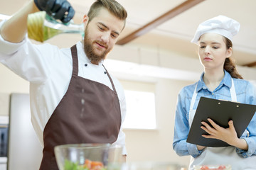 Low angle  portrait of two professional chefs working in restaurant kitchen together cooking and seasoning salad
