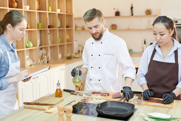 Team of professional chefs working in modern restaurant kitchen standing round wooden table and cooking delicious dishes together, copy space