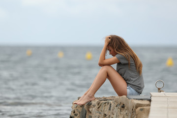 Sad teen alone with ocean in the background