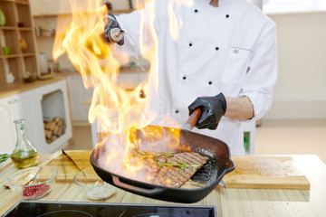 Closeup of flaming frying pan in hands of professional chef cooking in modern restaurant kitchen, copy space