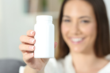 Woman hand showing a blank medicine bottle of pills