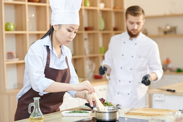 Portrait of female Asian chef cooking delicious dishes while working in modern restaurant kitchen, copy space