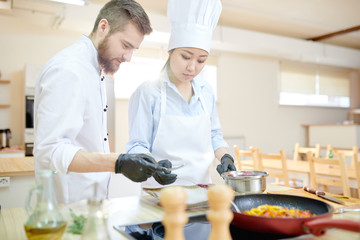Portrait of two professional chefs cooking delicious dishes in modern kitchen, copy space