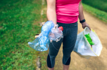 Plogging concept. Detail of unrecognizable girl showing the garbage she has collected. Selective focus on garbage in foreground
