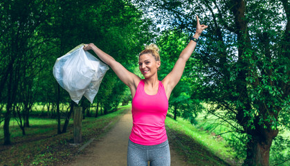 Happy girl with arms up showing the garbage bags she has collected doing plogging