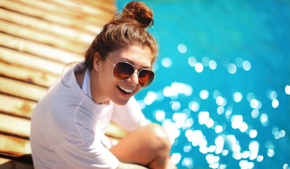 happy young woman in sunglasses sits on the pier and smiles, resting on the sea in Oludeniz, Fethiye, Turkey, portrait model