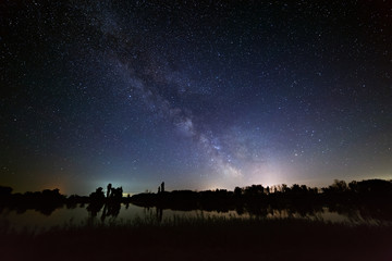 Space with stars in the night sky. The landscape with the river and trees is photographed on a long exposure.