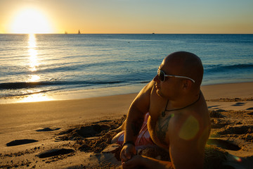 Man watching the sunset in the sand of Barbados Beach.  Idyllic afternoon at the beach in Barbados (Caribbean island): White sand, clear turquoise water with small waves and a sunny blue sky.