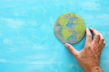 top view image of man hand holding earth globe over blue wooden background.