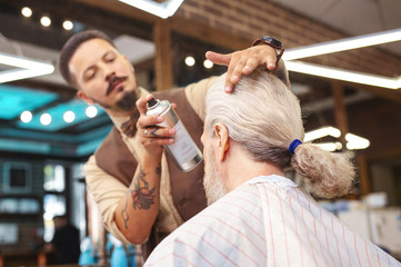Now its better. Serious bearded stylist holding bottle with spray while creating haircut