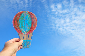 image of male hand holding air balloon against the sky. imagination and success concept.