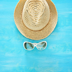 vacation and summer image with fedora beach hat and sunglasses over blue wooden background.