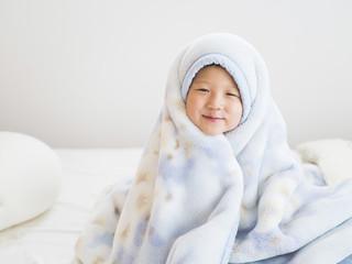 朝、布団にくるまって笑う男の子