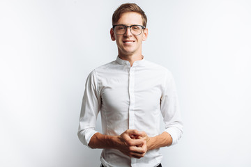 Obraz Portrait of young attractive guy in glasses, in white shirt, isolated on white background, for advertising, text insertion - fototapety do salonu