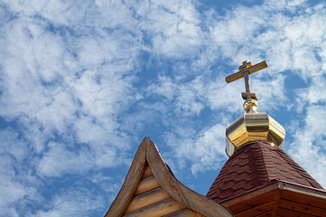 Cross on the golden dome of a small Russian Orthodox church background clear blue sky with sparse clouds. Symbol of faith
