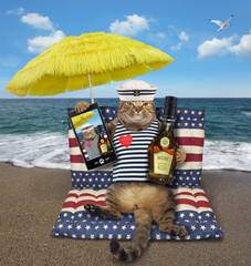The cat sailor with a abottle of rum and a smartphone sits on a air bed under a yellow umbrella on the beach.