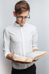 Man reading Bible, white background, book in hand close-up