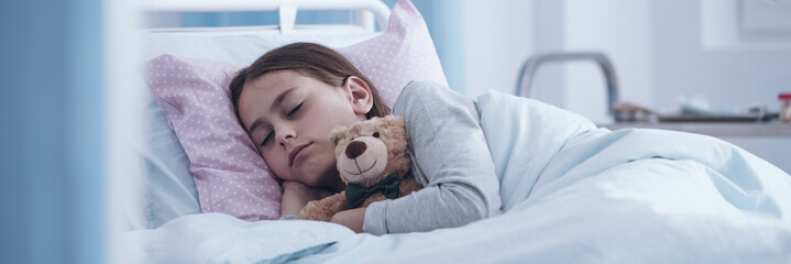 Panorama portrait of a sick little girl sleeping in a hospital bed with a teddy bear - view through the glass door
