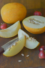 Cut ripe melon near red berries, knife on brown background - summer tasty food