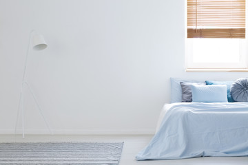 White lamp in bedroom interior with blue sheets on bed next to copy space. Real photo