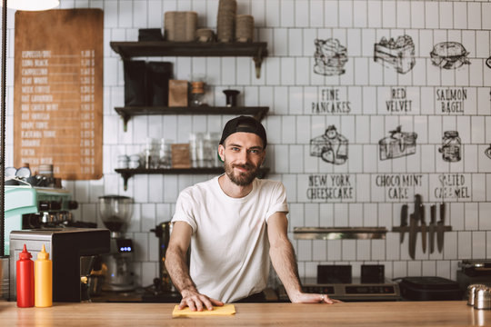 Smiling barista in cap standing and wiping bar counter while happily looking in camera in cafe