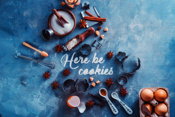 Header with baking tools and ingredients on a stone kitchen table. Here be cookies text made with flour. Food typography concept with copy space.