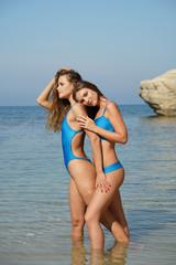 Two women in blue swimwear embracing