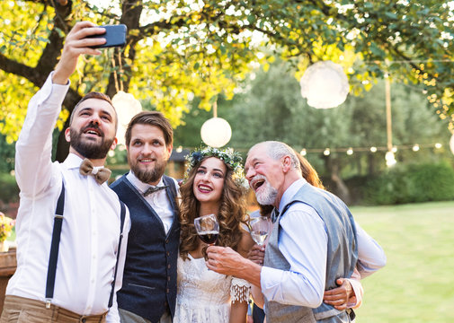 Bride, groom and guests with smartphone taking selfie outside at wedding reception.