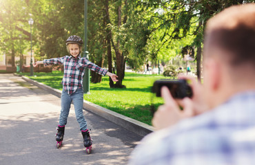 Father and daughter in roller skates and helmet
