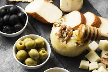 Snacks with wine - various types of cheeses, figs, nuts on a gray background