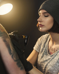 Young woman tattooist doing tattoo on shoulder