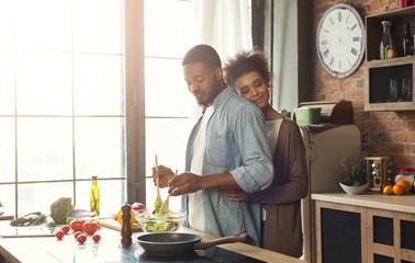 Loving black wife and husband preparing dinner in kitchen