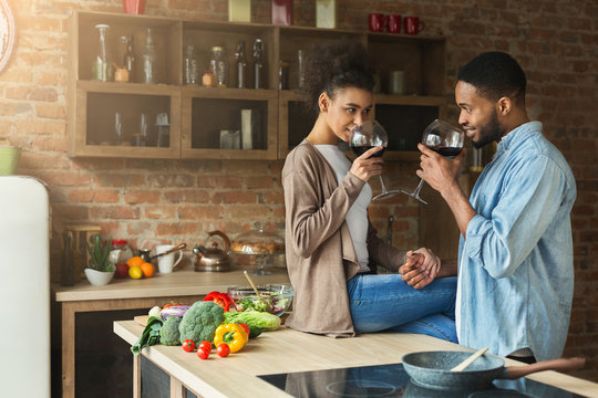Loving african-american couple drinking wine in kitchen.